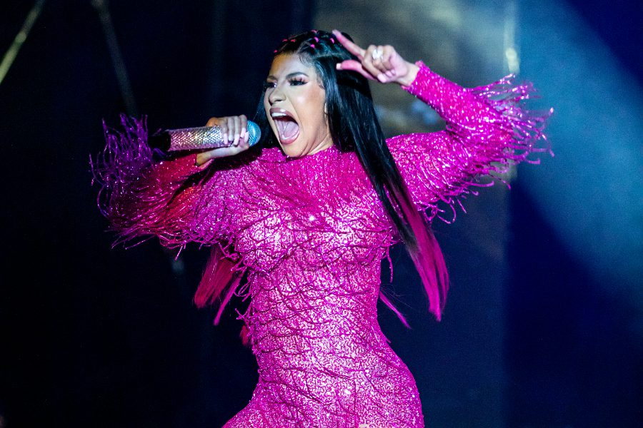 Cardi b rocks a long, covered-up magenta ensemble with hot pink ends on her hair