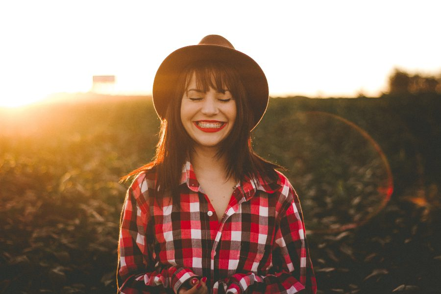 Girl wearing a brown hat and red flannel shirt in a field with the sun shining down on her to reap its hair benefits