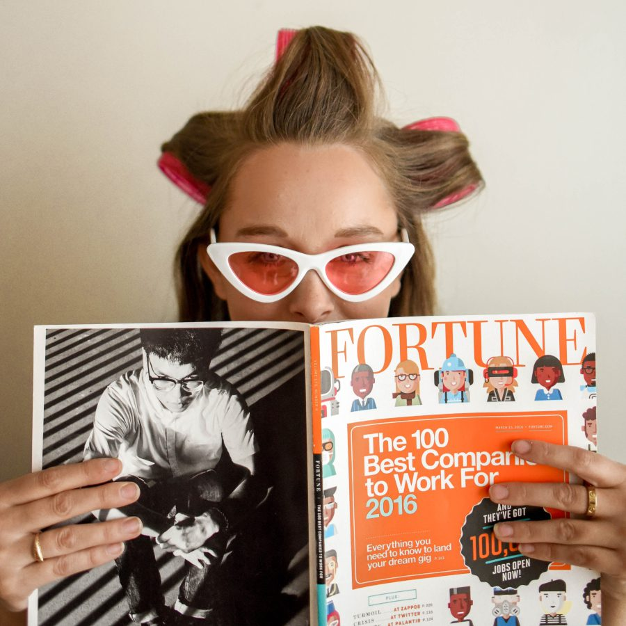White blonde girl with her hair in pink rollers covering her face with a magazine and wearing white sunglasses with pink lenses