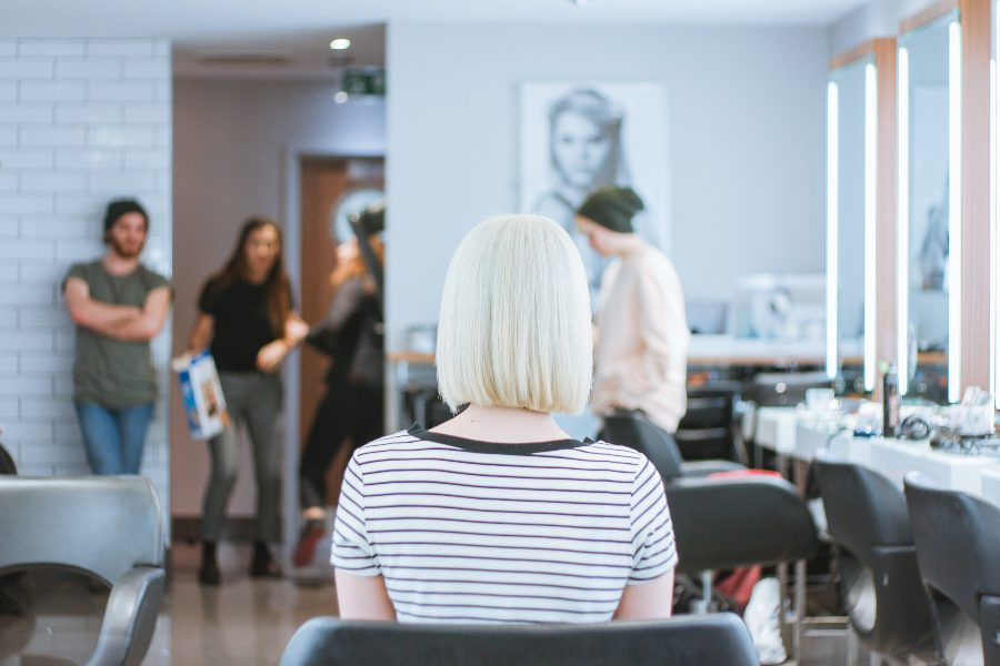 Woman with blunt, bleached bob sitting in a salon chair turned away from the camera